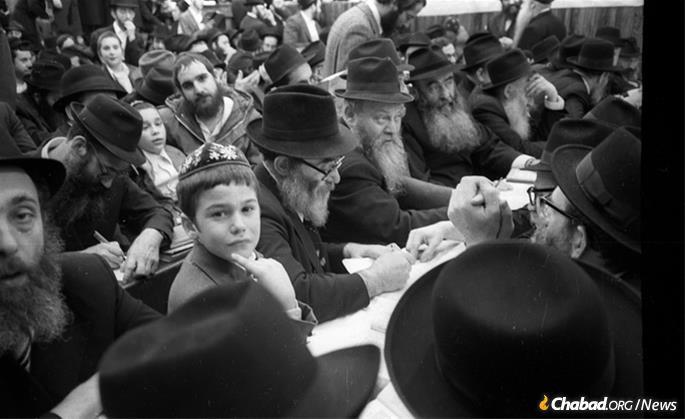 Attendees at a farbrengen of the Rebbe held in October 1979 take personal notes of the contents of the Rebbe's talk. (Photo: JEM/The Living Archive)