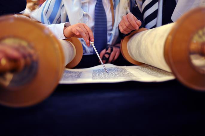A boy wearing Sephardi tefillin reading from an Ashkenazi Torah.
