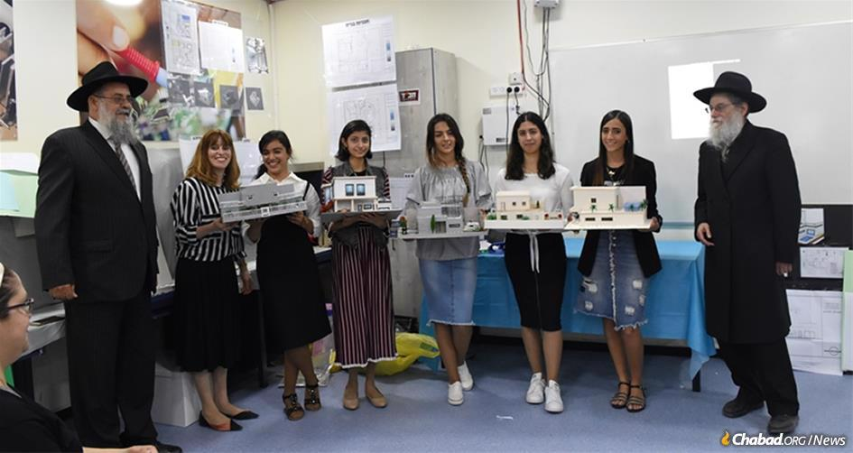 First-year students at the Chabad School of Architecture and Design in Ashkelon, Israel, display model homes they made. The school's curriculum combines classes in Chassidus and other Torah subjects with courses leading to a degree. The young women are flanked by Mordechai Gorelik, left, former head architect for the city of Ashkelon, now a teacher at the school, and Rabbi Menachem Lieberman, director of Chabad of Ashkelon.
