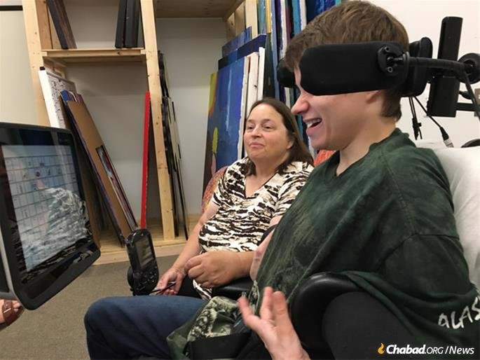 Felicia Bowers using her Tobii Dynavox tablet with Eyegaze eye tracking software, as her mother, Tina Bowers, looks on.