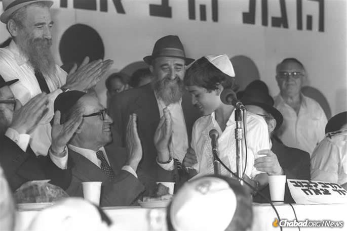 The author, Avraham Godin, was arrested by Soviet occupying authorities in 1941 and released from the Gulag in 1956. He came to Israel a decade later, where he became secretary of Tzierei Agudas Chabad of Israel. Here, he is pictured (center) in 1977 on the dais of the communal bar mitzvahs for IDF war orphans, watching as Israeli Prime Minister Menachem Begin applauds Shai Cohen. Photo: Moshe Milner/Israel Government Press Office.