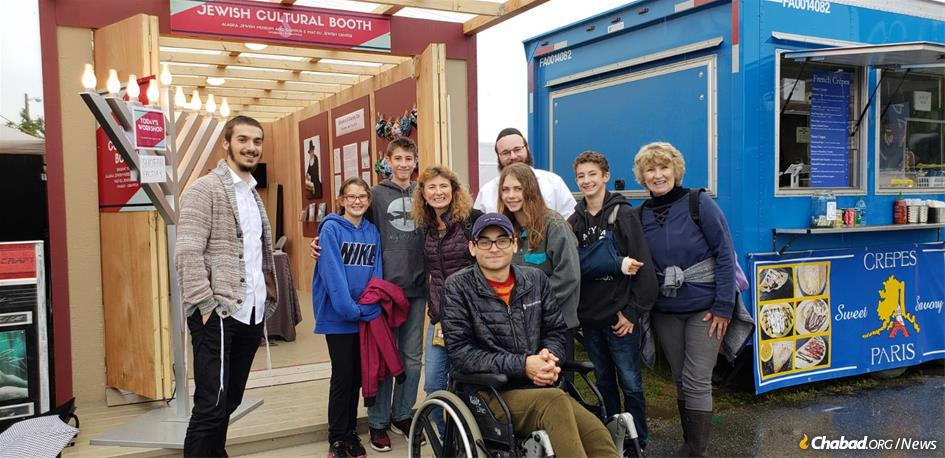 Rabbinical students Rabbi Ari Herson, left, and Rabbi Shmueli Butler, center, with visitors to the Jewish Cultural Booth at the Alaska State Fair.