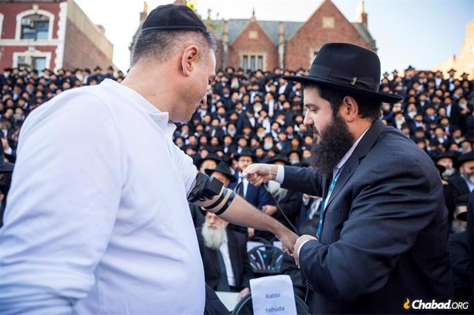 Rabbi Mendy Kotlarsky, right, of Brooklyn, New York, puts on tefillin with a visitor. (Photo: Mendel Grossbaum / Chabad.org)