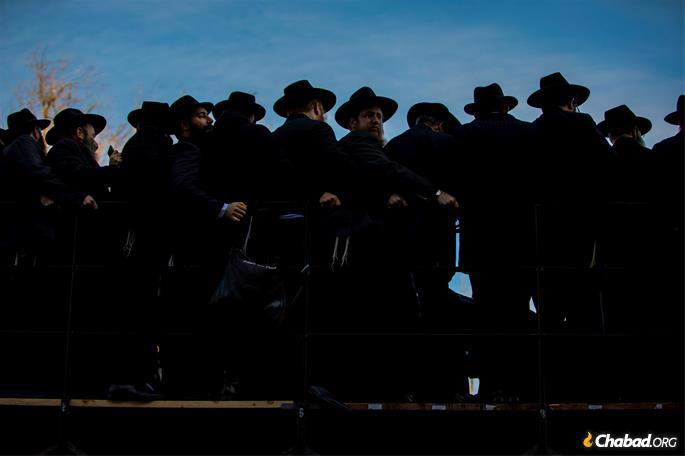 Rabbi Tzvi Rivkin, center, of Bangalore, India, looks on amid a sea of black hats as they pose for a group photo in front of Chabad-Lubavitch world headquarters. (Photo: Mendel Grossbaum / Chabad.org