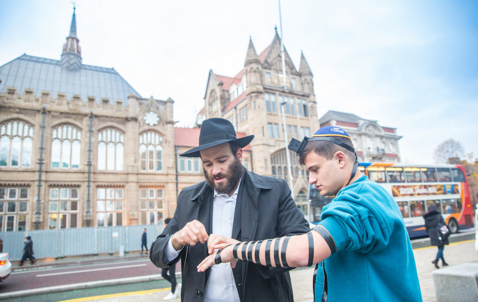 Putting on tefillin in Manchester, U.K. (Photo by Bentzi Sasson)