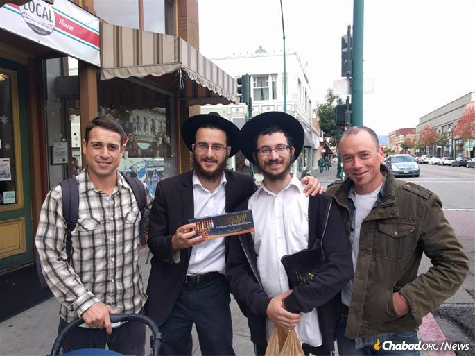 Students Levi Shmotkin and Mendel Kalmanson put tefillin on and give menorahs to Jewish passersby in Alameda, Calif.