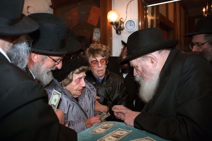 Bubby Miriam Greenhut receiving a dollar from the Rebbe. (JEM/The Living Archive)