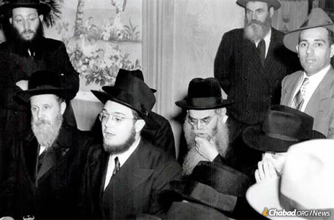 The Lubavitcher Rebbe, seated at right, and the Rebbe's brother-in-law, Rabbi Shemaryahu Gurary, seated at left, flank Rabbi Mendel Baumgarten at his wedding.
