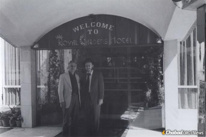 """Hecht and an Iranian Jew pose outside of the Royal Gardens Hotel. Before the revolution, the hotel was owned by the prominent Jewish Berookhim family, one of whom, Ebrahim """"Ebi,"""" was arrested, accused of being a Zionist and killed by the Islamic Republic of Iran in July of 1980. (Photo: Courtesy NCFJE)"""