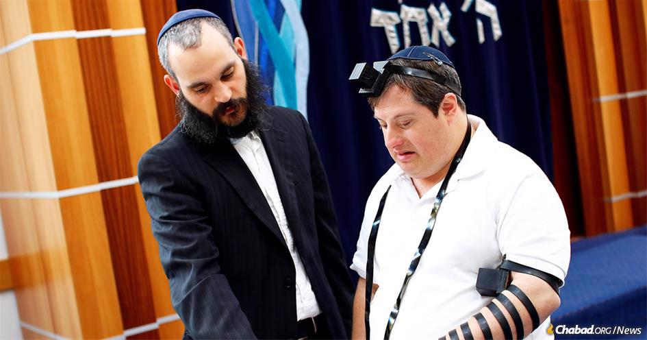 Rabbi Reuvi Cooper, left, youth director at the Chabad House of Malvern in Melbourne, Australia, helps Zac Chester put on tefillin before the city's ShabbaTTogether event. (Photo: Peter Haskin)