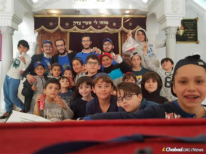 Children gather for an event in the Chabad synagogue. A plaque on the right honors the memory of Rabbi Leibel Raskin.
