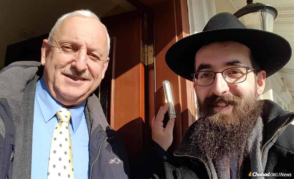 Rabbi Heshy Ceitlin with Arkady Samoylov, who had mezuzahs affixed on the home he has lived in for many years.