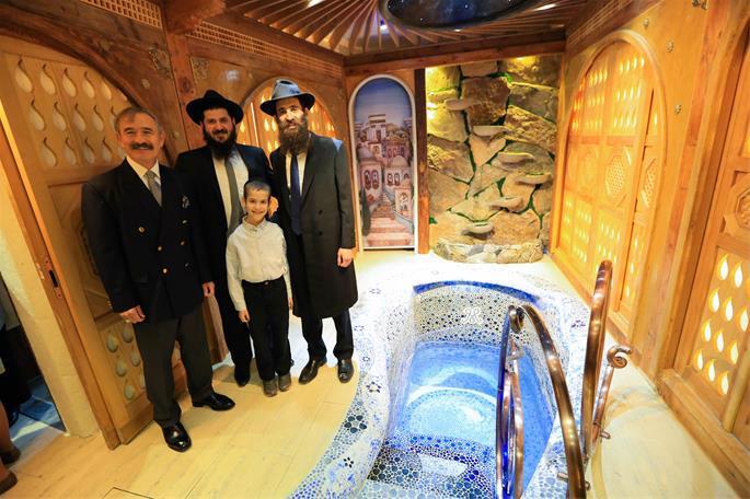 Rabbi Litzman, at right, Rabbi Mendy Kotlarsky and guests at the uniquely designed mikvah.