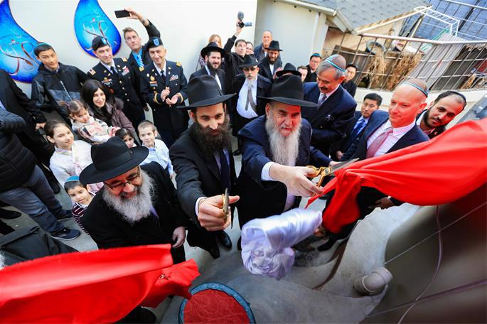 At the ribbon-cutting ceremony are Rabbi Osher Litzman, center left, Rabbi Moshe Kotlarsky, center right, and other dignitaries, family and guests.