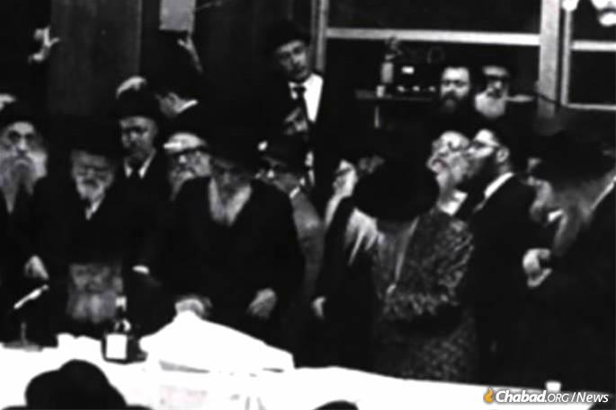 "The Skulener Rebbe, front, second from right, stands as the Lubavitcher Rebbe, seated left, delivers a Chassidic ""maamar"" (discourse)."