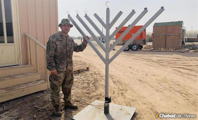 Cohen in Kuwait with the menorah he obtained with the help of the Aleph Institute.