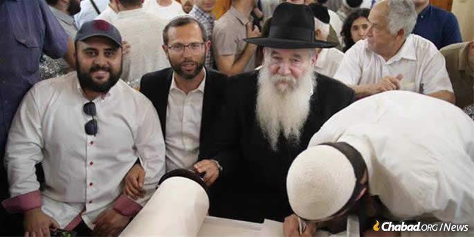 Rabbi Yitzchok Kogan watches as the final letters are inscribed in a Torah scroll donated by the Bolshoya Bronnaya Synagogue in Moscow to a yeshivah in south Tel Aviv.