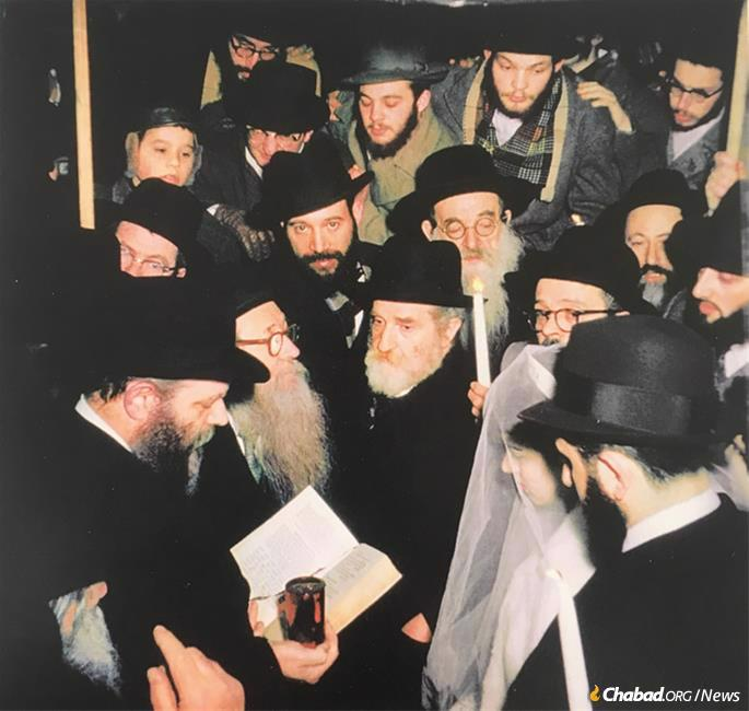 """In a private audience with the Rebbe, Raskin asked him to officiate at his wedding. The Rebbe, who had requested of Raskin that he grow a beard, replied: """"If you do what I ask of you, I'll do what you ask of me."""" Raskin agreed. The Rebbe (on left, holding wine) officiating on Feb. 9, 1959."""