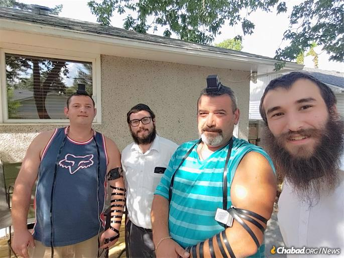 """Rabbi Mendel Super, center, and Rabbi Eliyahu Citron, right, heard there was a Jewish family in Weyburn, an hour and 20 minutes out of Regina with a population of 10,000. They parked outside City Hall to see if perhaps they knew of any other Jews living there. As they stepped out of their car, another car pulled up alongside them. Rolling the window down, the driver called out Mah shlomcha? (""""How are you?"""" in Hebrew). Excited, Super went over and asked him if he was Jewish, and sure enough, he was. He invited the young rabbis to follow him to his house, where they spent a while with him and his son discussing all things Jewish. They later discovered that this was, in fact, the family they had heard about before, but the address they had was wrong. Had he not spotted them, they would not have found him."""