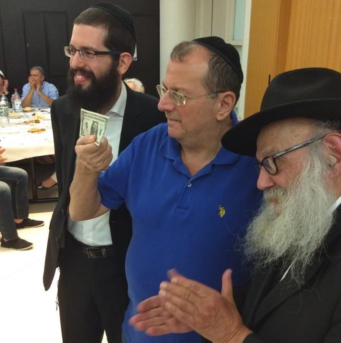 Michel Ladezenski é sorteado com um dolar do Rebe, na presença do palestrante Rabino Groner, secretário do Rebe