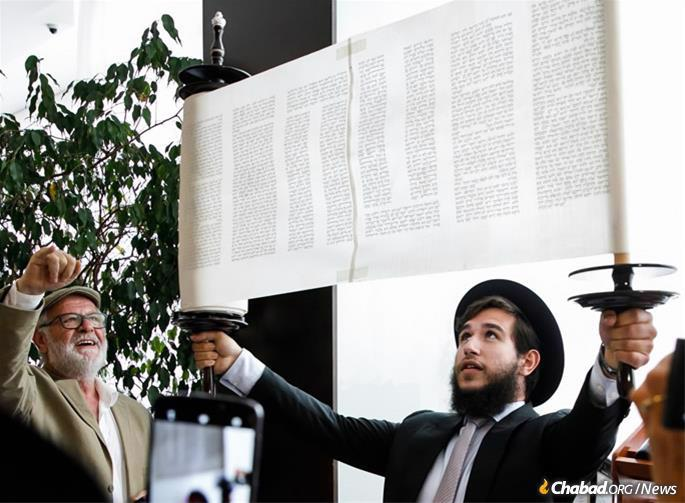 Rabbi Menachem Mendel Myers, the oldest son of Myers family and Tzali's brother, raises the Torah scroll after the last letter was inscribed.