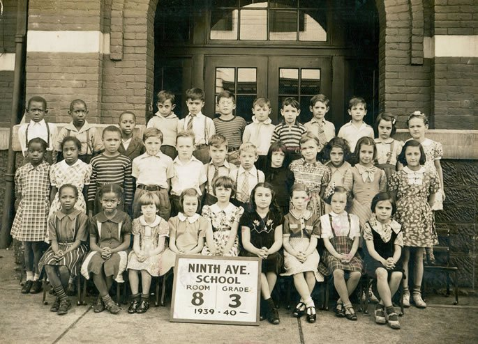 Sara in grade school, sitting front row, first on the right.