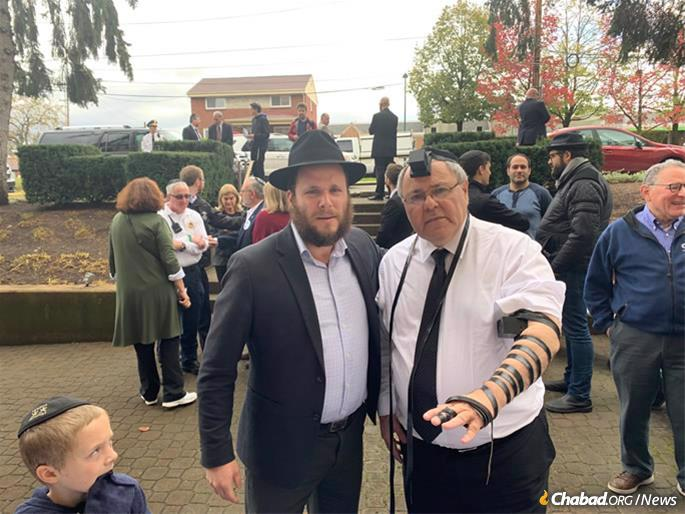 Consul General of Israel in New York Dani Dayan (right) dons tefillin at a ceremony at the Tree of Life in Pittsburgh, commemorating the 11 Jewish worshippers who were shot and killed there a year ago.
