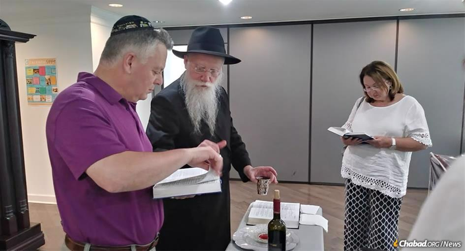 Rabbi Shmuel Notik makes the traditional blessings as Ilya, who was born in the former Soviet Union, is given the Hebrew name Yosef Yitzchak Meir, following his brit milah. Yosef Yitzchak Meir's wife, Alina, looks on.