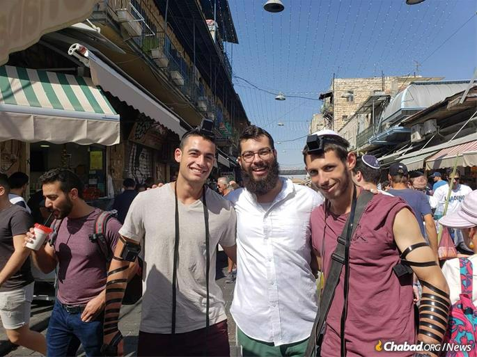 Gabi Kaufman, center, a recent student president of Chabad at the University of Pittsburgh and now a student at the Mayanot Institute of Jewish Studies in Jerusalem, helps others put on tefillin at the Machane Yehuda open-air market.