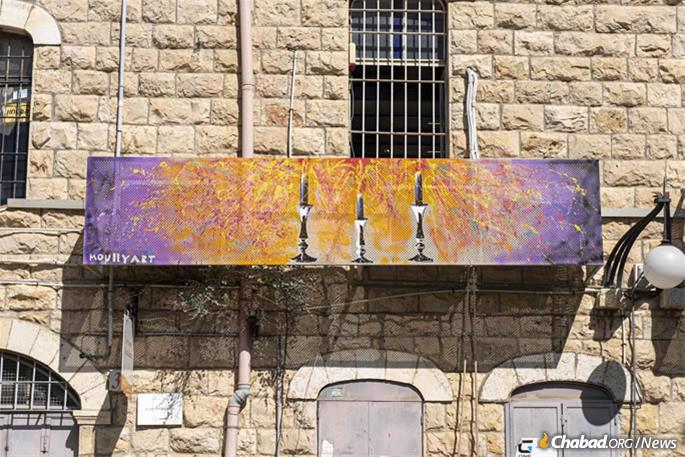 """Shabbat candles represent the seventh day in a """"Seven Days of Creation"""" collaboration on the Artist's Colony building just outside of the Old City."""