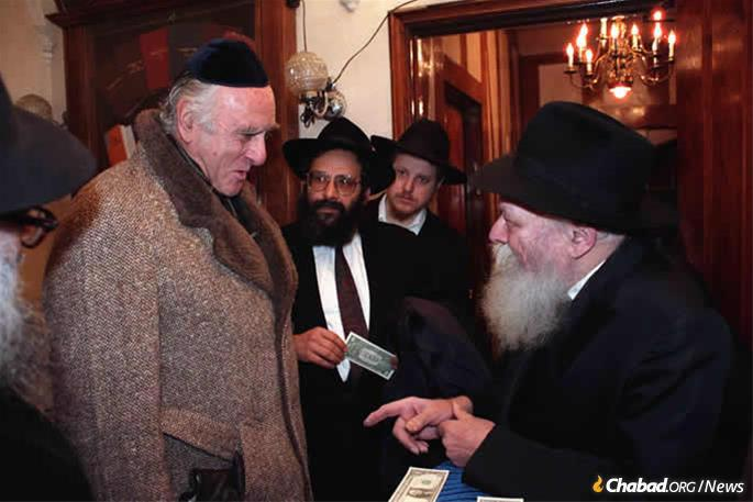 Weinstein receives a dollar and a blessing from the Rebbe, Rabbi Menachem M. Schneerson, on Dec. 17, 1989, as Rabbi Sholom Lipskar looks on. Weinstein was on his way to testify before the Federal Sentencing Commission. (Photo: Jewish Educational Media/The Living Archive)
