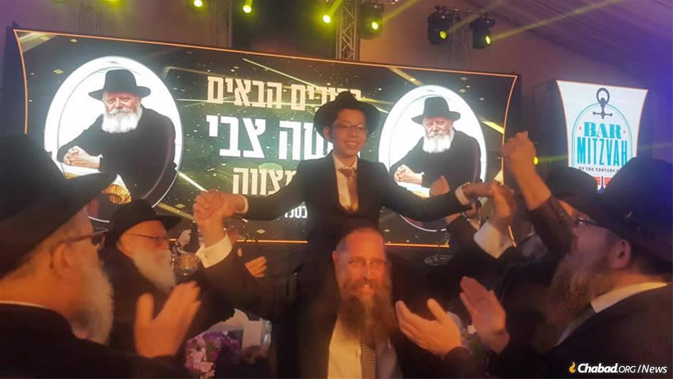 A celebratory bar mitzvah crowd dances with Moshe Holtzberg, orphaned in the Mumbai Chabad center massacre that took the lives of his parents 11 years ago this week.