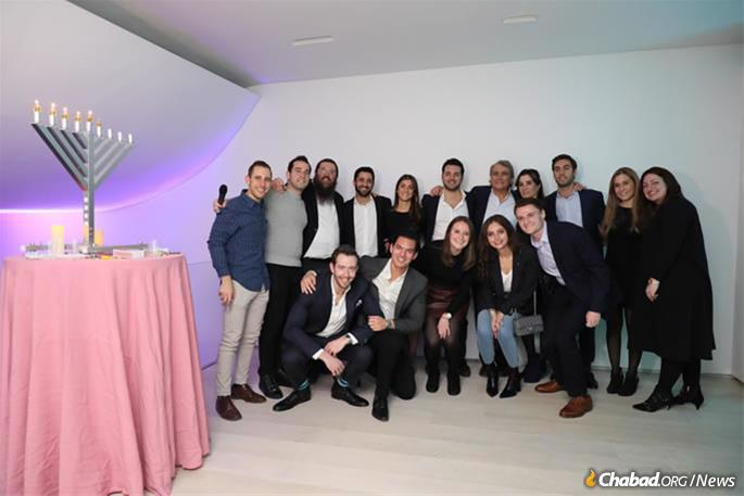 Participants at a Chabad Young Professionals UES Chanukah event last year led by Rabbi Yosef Wilhem, third from left, and Devora Wilhelm, right. (File photo)