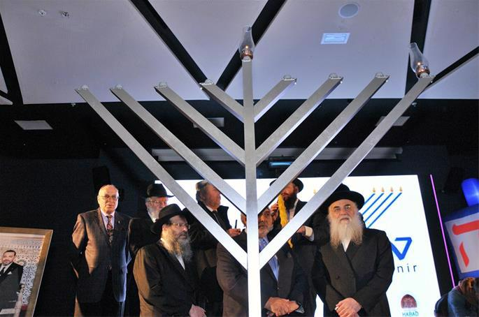 Visiting rabbis and local Jewish leaders stand with the menorah before them.