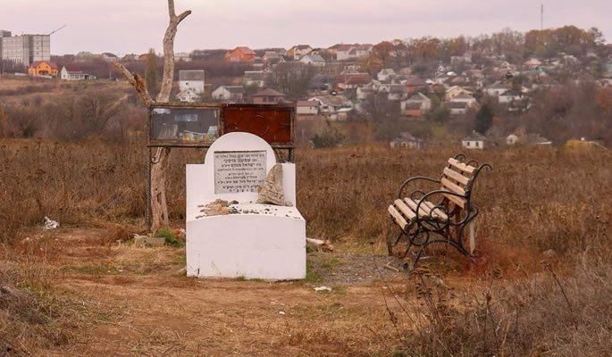 A cemetery in Berdichev, a grave of one of the righteous with a tree that is believed to bring blessings for children. Pieces of the tree are often cut of by the visitors, leaving it looking bare.