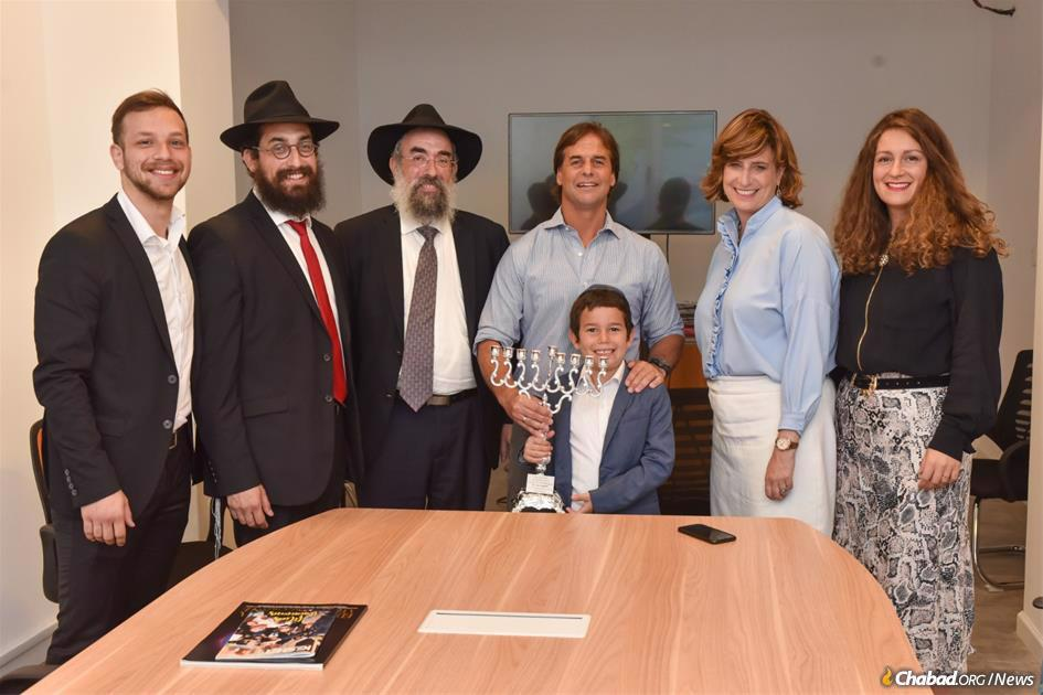 Uruguay's president-elect Luis Lacalle Pou, center, receives a silver Chanukah menorah from Chabad. Attending, from left: Ian Bruck, representing Chabad youth programs; Rabbi Mendy Shemtov; Rabbi Eliezer Shemtov; Rochel Shemtov; and Musya Shemtov. Young Shneur Shemtov handed the menorah to Lacalle Pou as his father did at his age 30 years ago to then President Luis Alberto Lacalle Herrera, the father of the president-elect. (Photo: Andrés Aksler)