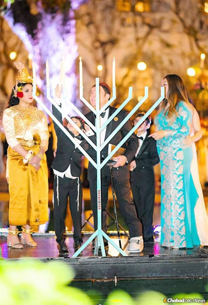 Elior (in traditional Cambodian dress) with her parents, Ray and Susie Koroghli, and her brothers at a Chanukah menorah-lighting during the bat mitzvah celebration. (Photo: Kang Predi/Teh Ranie)