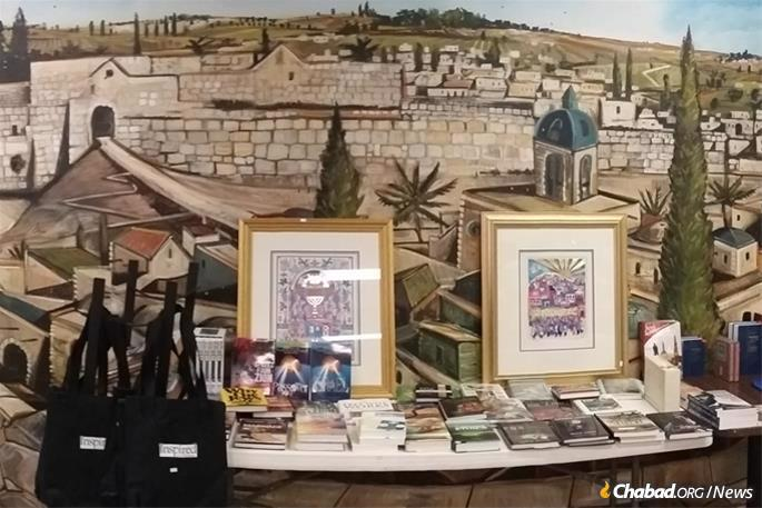 The deli is also serves as a Jewish bookstore, featuring a long table stacked with Jewish titles, with a mural of Jerusalem's Old City in the background.