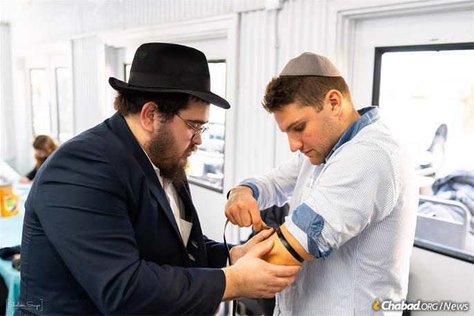 Donning tefillin at the Ohel. (Photo: Sholem Srugo)