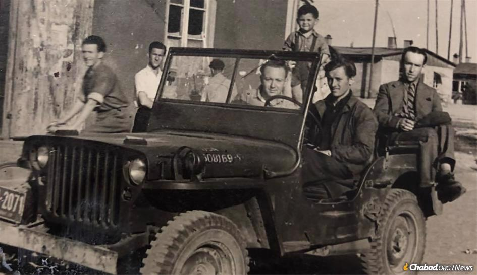 Henry Eisen in 1947, behind the wheel of a Jeep in a Displaced Persons' Camp in Foehrenwald, Germany, with fellow survivors two years after the defeat of the Nazis.