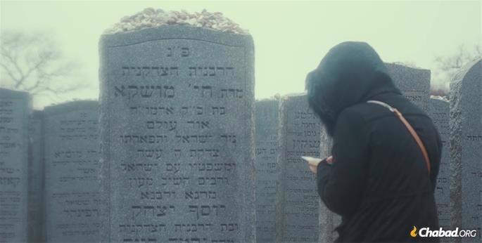 A woman prays at the Rebbetzin's resting place.