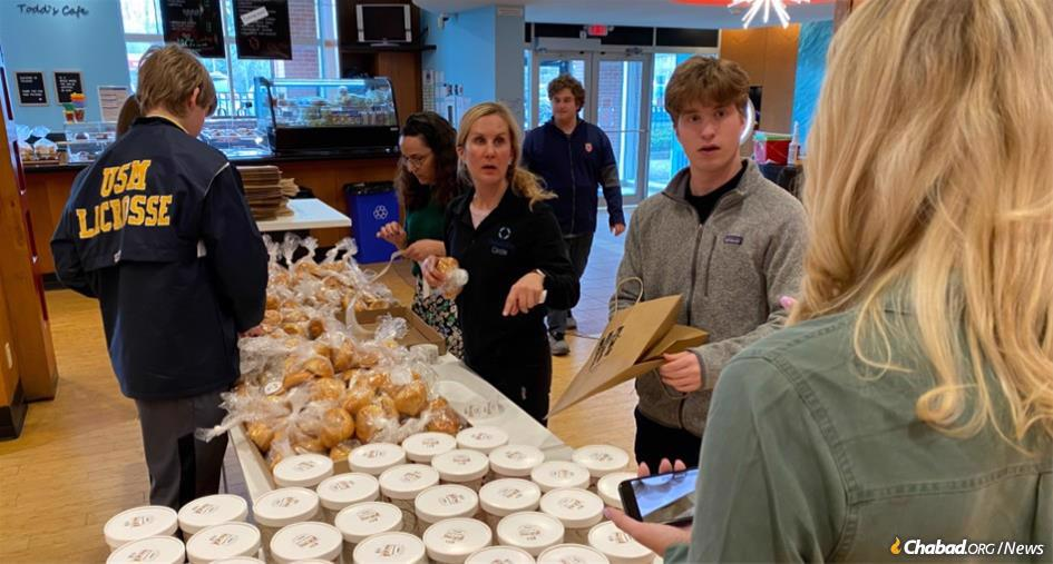 At the Friendship Bakery in Wisconsin, Alex Kimmel, right, helps prepare care packages to be dropped off at the doorsteps of homebound kids with special needs. Actual visits will be taking place online.
