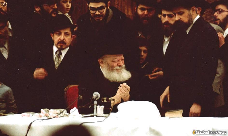 Rabbi Mordechai Gurary, center left, at a farbrengen with the Rebbe.