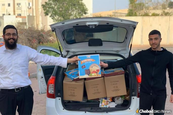 Distributing matzah this week in Dimona, Israel. As stringencies increase, Tzeirei Agudat Chabad, the movement's umbrella organization in the Israel, has partnered with the central matzah bakery in Kfar Chabad and the national post to ensure that matzah still gets to where it needs to go.