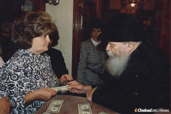 Mrs. Rivkin receives a dollar and a blessing from the Lubavitcher Rebbe.