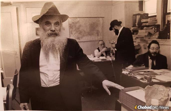 In the office of Lishkas Ezras Achim, circa 1980s. Forefront: Rabbi Moshe Levertov, a founder and prime mover of the organization. Sitting at the desk on the right is Rabbi Shloma Zuntz, who came on board to direct the organization as it grew. Korf can be seen at his desk in the background. (Credit: Archives of Ezras Achim)