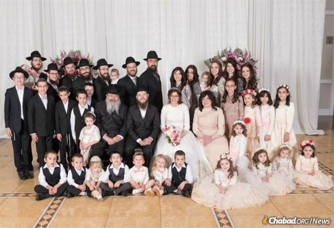 At a family wedding with her husband, Rabbi Yitzchok Charytan, children and grandchildren.