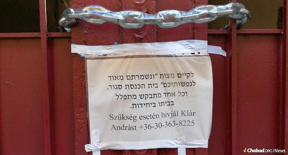 "A sign attached to the padlocked door of the Shas Chevra Lubavitch synagogue in Budapest, Hungary, reads: ""To fulfill the mitzvah of 'you shall guard your lives very well,' the synagogue is closed. Everyone is requested to pray individually at home."" (Photo: Tamás-Haim www.tfilin.hus)"