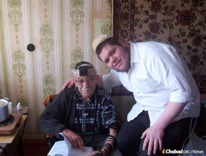 Kopman on a visit to Russia, helping an elder to put on tefillin.