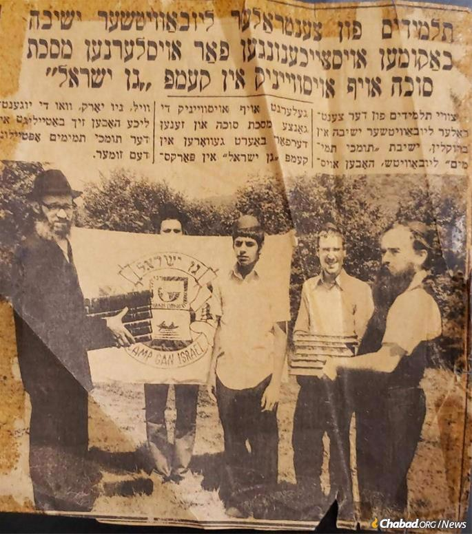 Giving a prize to a camper who completed a tractate of the Talmud at camp Gan Yisroel in Parksville, N.Y. On the right is Rabbi Abraham Shemtov.